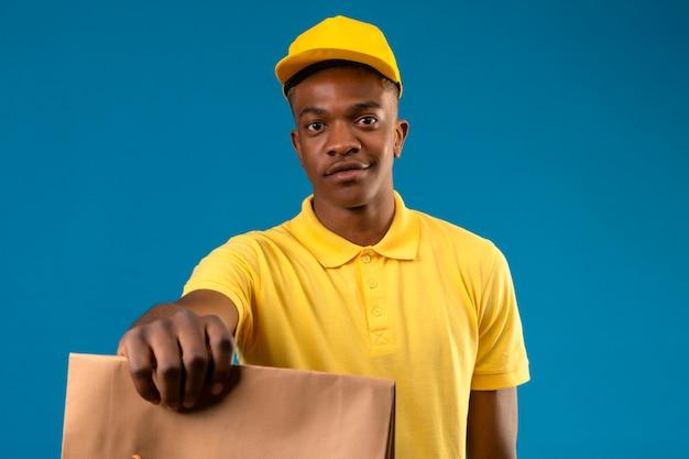 Dostawa Afroamerykanin Mężczyzna W żółtej Koszulce Polo I Czapce, Trzymając I Wyciągając Papierowy Pakiet Uśmiechnięty Przyjazny Na Odosobnionym Niebieskim Darmowe Zdjęcia