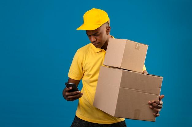 Dostawa Afroamerykanin Mężczyzna W żółtej Koszulce Polo I Czapce, Trzymając Kartony, Patrząc Na Ekran Swojego Telefonu Komórkowego Stojącego Na Niebiesko Darmowe Zdjęcia