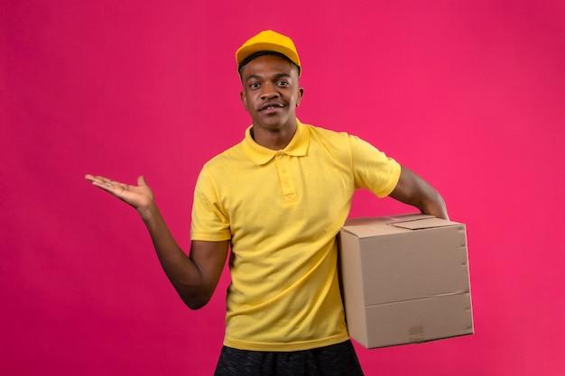 Dostawa Afroamerykanin Mężczyzna W żółtej Koszulce Polo I Czapce, Trzymając Pakiet Pudełkowy Prezentując I Wskazując Dłonią Stojącą Na Na Białym Tle Różowy Darmowe Zdjęcia