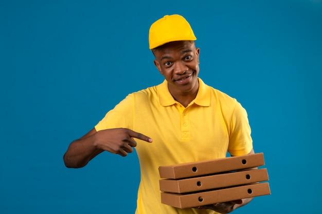 Dostawa Afroamerykanin Mężczyzna W żółtej Koszulce Polo I Czapce, Trzymając Pudełka Po Pizzy I Wskazując Palcem Na Nich Uśmiechnięty Przyjazny Stojący Na Odosobnionym Niebieskim Darmowe Zdjęcia