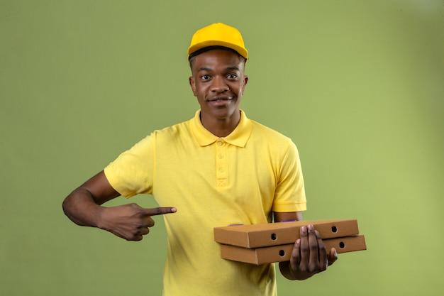 Dostawa Afroamerykanin Mężczyzna W żółtej Koszulce Polo I Czapce, Trzymając Pudełka Po Pizzy I Wskazując Palcem W Bok Uśmiechnięty Przyjazny Stojący Na Odizolowanej Zieleni Darmowe Zdjęcia
