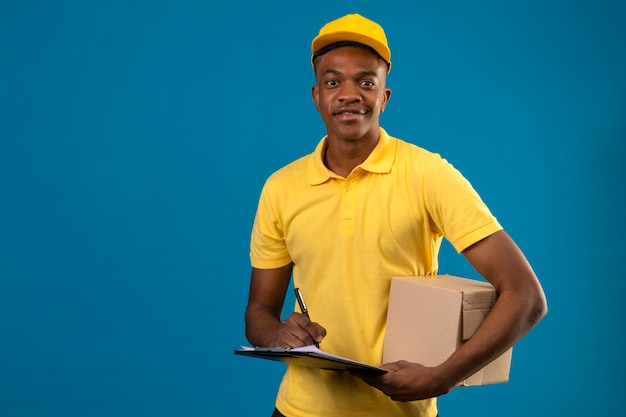 Dostawa Afroamerykanin Mężczyzna W żółtej Koszulce Polo I Czapce, Trzymając Schowek I Karton Z Pewnym Uśmiechem Stojący Na Odosobnionym Niebieskim Darmowe Zdjęcia