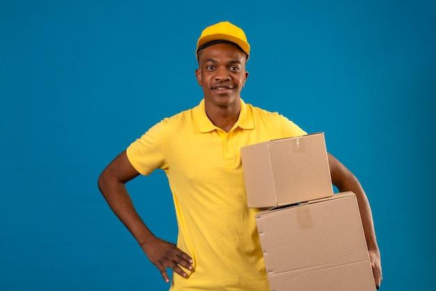 Dostawa Afroamerykanin Mężczyzna W żółtej Koszulce Polo I Czapce Trzymającej Kartony Z Przyjaznym Uśmiechem Stojącym Na Odosobnionym Niebieskim Darmowe Zdjęcia