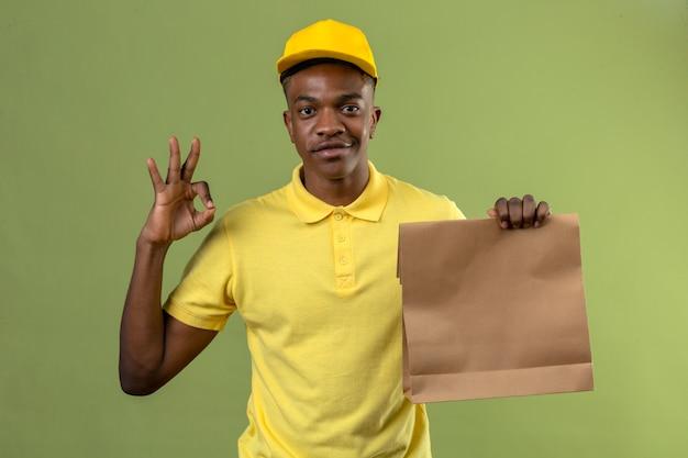 Dostawa Afroamerykanin Mężczyzna W żółtej Koszulce Polo I Czapce Trzymającej Papierowy Pakiet Patrząc Radośnie Uśmiechnięty Robi Ok Znak Na Zielono Darmowe Zdjęcia