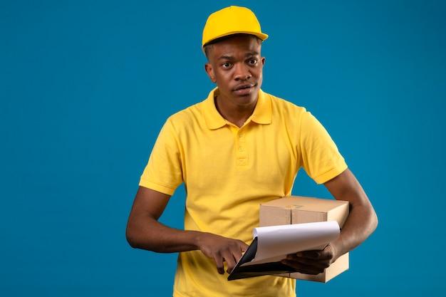 Dostawa Afroamerykanin Mężczyzna W żółtej Koszulce Polo I Czapce Trzymający Karton I Schowek Skoncentrowany Na Zadaniu Stojącym Na Odosobnionym Niebieskim Darmowe Zdjęcia