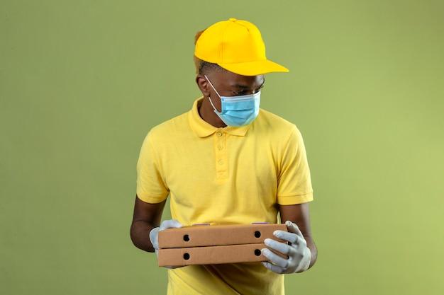 Dostawa Afroamerykanin W żółtej Koszulce Polo I Czapce Na Sobie Medyczną Maskę Ochronną, Trzymając Pudełka Po Pizzy Patrząc Na Bok Z Poważną Twarzą Stojącą Na Zielono Darmowe Zdjęcia
