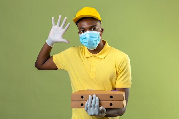 Dostawa Afroamerykanin W żółtej Koszulce Polo I Czapce Na Sobie Medyczną Maskę Ochronną, Trzymając Pudełka Po Pizzy Pokazujące Numer Pięć Z Otwartą Ręką Stojącą Na Zielono Darmowe Zdjęcia