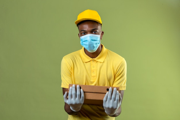 Dostawa Afroamerykanin W żółtej Koszulce Polo I Czapce Na Sobie Medyczną Maskę Ochronną, Trzymając Pudełka Po Pizzy Z Uśmiechem Na Twarzy Stojącej Na Zielono Darmowe Zdjęcia