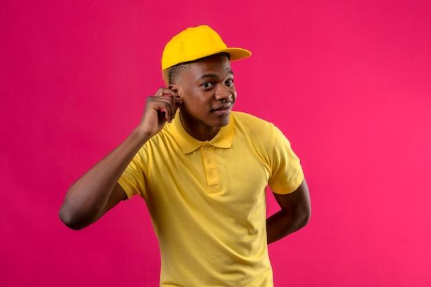 Dostawa Afroamerykanin W żółtej Koszulce Polo I Czapce Trzymającej Rękę Przy Uchu, Próbując Słuchać Rozmowy Kogoś Stojącego Na Różowo Darmowe Zdjęcia