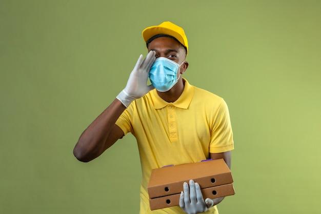 Dostawa Afroamerykanin W żółtej Koszulce Polo I Czapce W Medycznej Masce Ochronnej Trzymający Pudełka Po Pizzy Krzyczący Lub Wzywający Kogoś Ręką W Pobliżu Ust Stojącego Na Zielono Darmowe Zdjęcia