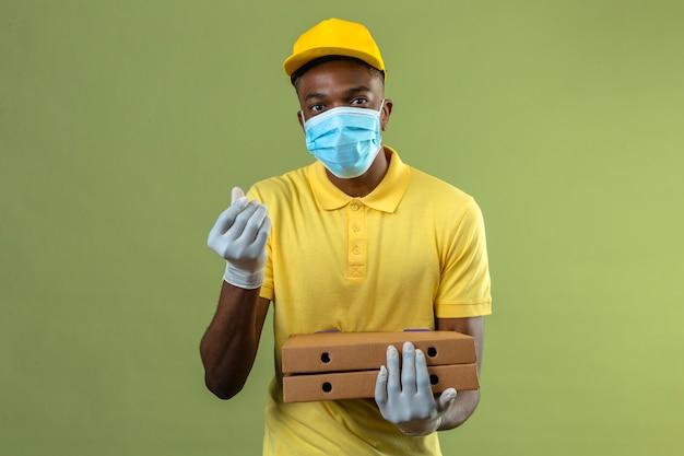 Dostawa Afroamerykanin W żółtej Koszulce Polo I Czapce W Medycznej Masce Ochronnej, Trzymający Pudełka Po Pizzy, Robiąc Gest Pieniędzy Ręką Czekającą Na Płatność Stojącą Na Zielono Darmowe Zdjęcia