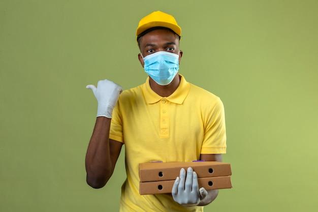 Dostawa Afroamerykanin W żółtej Koszulce Polo I Czapce W Medycznej Masce Ochronnej Trzymający Pudełka Po Pizzy Z Poważną Twarzą Skierowaną W Bok Z Kciukiem Stojącym Na Zielono Darmowe Zdjęcia