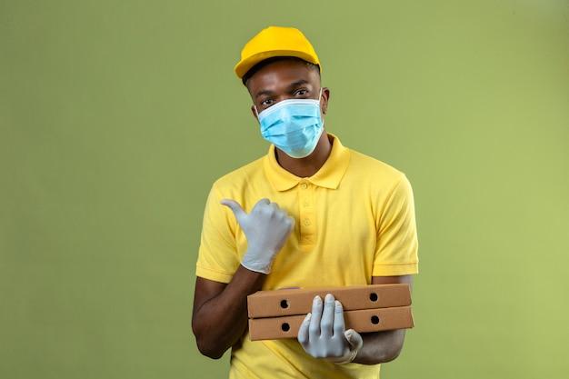 Dostawa Afroamerykanin W żółtej Koszulce Polo I Czapce W Medycznej Masce Ochronnej Trzymający Pudełka Po Pizzy Z Uśmiechem Na Twarzy Wskazujący W Bok Z Kciukiem Stojącym Na Zielono Darmowe Zdjęcia