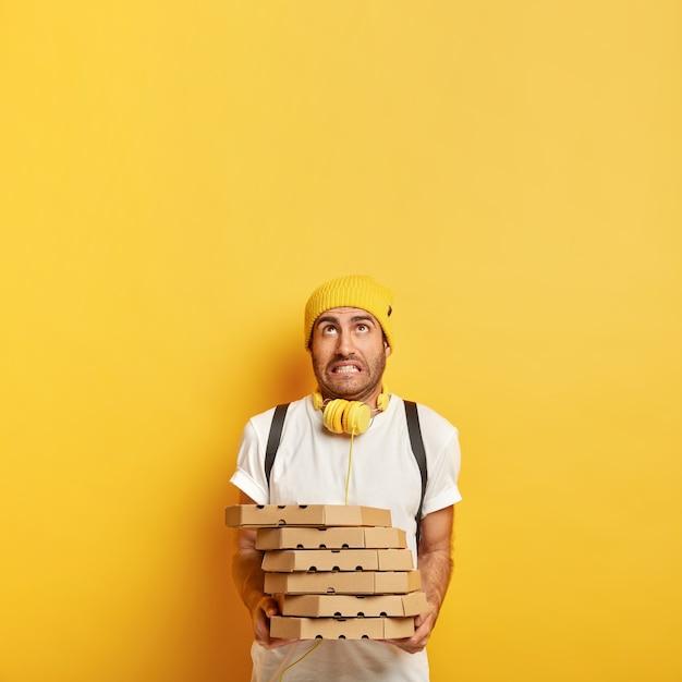 Dostawa Do Domu Z Pizzerii. Zmęczony Mężczyzna Ubrany W Zwykły Strój, Trzyma Stos Kartonów, Pozuje Z Zamówieniem Jedzenia. Młody Człowiek Pizzy Pracuje Jako Sprzedawca Kurierski, Koncentrując Się Powyżej Na Przestrzeni Kopii Darmowe Zdjęcia