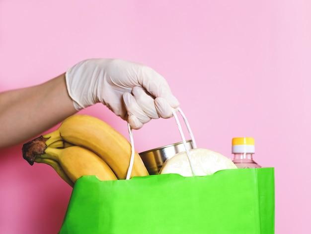 Dostawa Jedzenia. Ręce W Rękawiczkach. Koronawirus. Torba Papierowa Z Jedzeniem Premium Zdjęcia