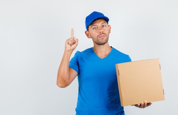 Dostawa Mężczyzna Trzyma Karton Z Palcem W Niebieskiej Koszulce Darmowe Zdjęcia
