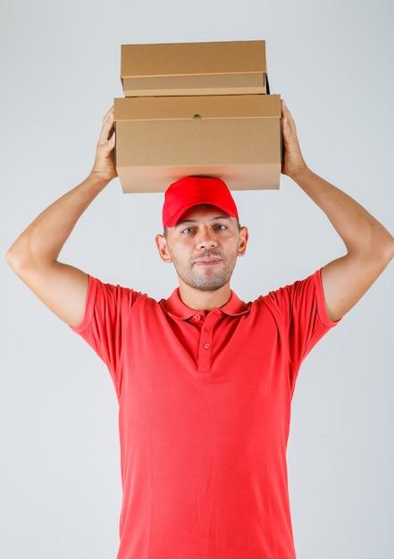 Dostawa Mężczyzna Trzyma Kartony Nad Głową W Widoku Z Przodu Jednolite Czerwony. Darmowe Zdjęcia