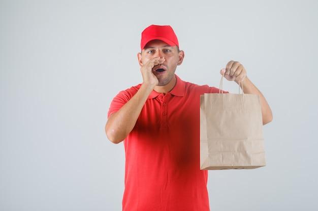 Dostawa Mężczyzna Trzyma Papierową Torbę I Gestykuluje W Czerwonym Mundurze Widok Z Przodu. Darmowe Zdjęcia