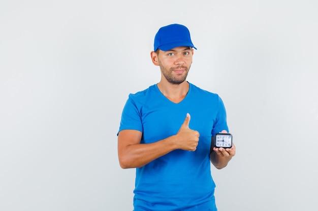 Dostawa Mężczyzna Trzyma Zegar Z Kciukiem Do Góry W Niebieskiej Koszulce Darmowe Zdjęcia
