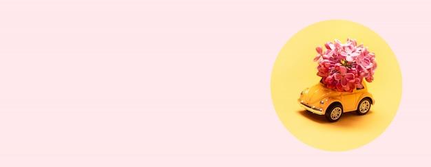 Dostawa świeżych kwiatów na wakacje. zabawka żółty samochód z gałęzi kwiatu bzu. Premium Zdjęcia