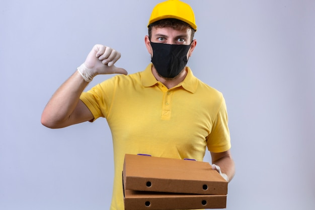 Dostawca W żółtej Koszulce Polo I Czapce W Czarnej Masce Ochronnej Trzymający Pudełka Po Pizzy Wskazujący Na Siebie Kciukiem Wyglądający Na Pewnego Siebie Zadowolonego Stojącego Na Odizolowanej Bieli Darmowe Zdjęcia
