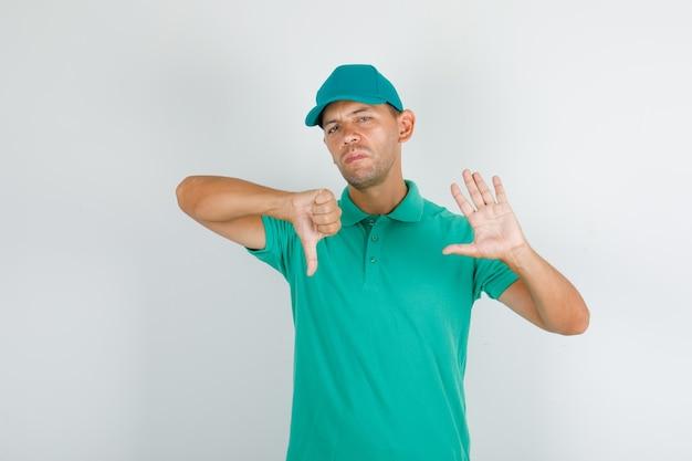 Dostawczyni Gestykulujący Nie I Pokazujący Kciuk W Dół W Zielonej Koszulce I Czapce Darmowe Zdjęcia