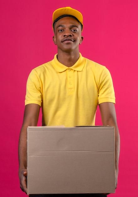 Dostawy Afroamerykanin W żółtej Koszulce Polo I Czapce Trzyma Karton, Patrząc Pewnie Stojąc Na Różowo Darmowe Zdjęcia