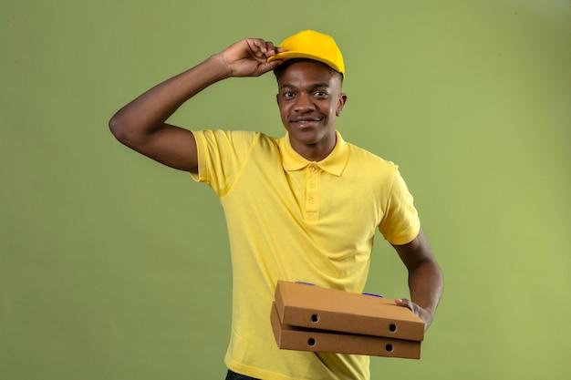 Dostawy Afroamerykanin W żółtej Koszulce Polo I Czapce Trzymającej Pudełka Po Pizzy Pozdrowienia Dotykając Jego Czapki Uśmiechnięty Przyjazny Stojący Na Zielono Darmowe Zdjęcia