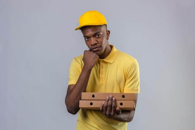 Dostawy Afroamerykanin W żółtej Koszulce Polo I Czapce Trzymającej Pudełka Po Pizzy Z Ręką Na Brodzie Czeka Z Poważną Miną Darmowe Zdjęcia