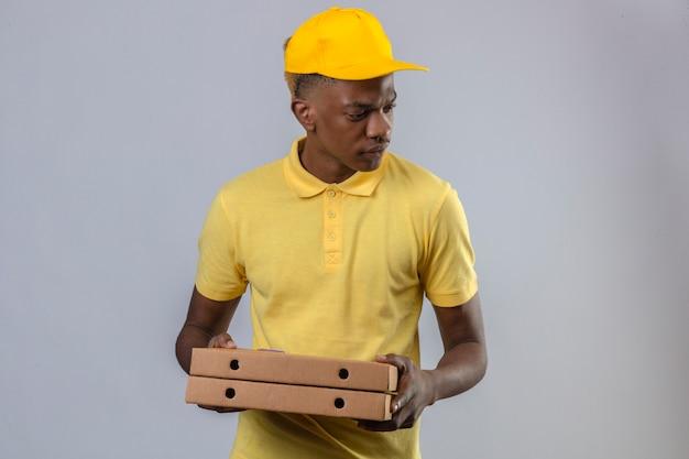 Dostawy Afroamerykanin W żółtej Koszulce Polo I Czapce Trzymający Pudełka Po Pizzy Patrząc Na Bok Z Marszczoną Twarzą Stojącą Darmowe Zdjęcia