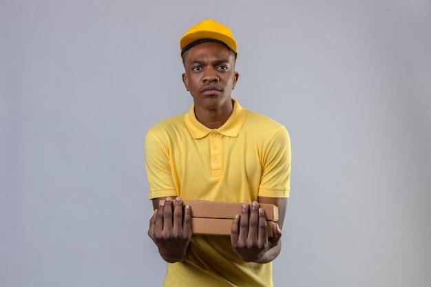 Dostawy Afroamerykanin W żółtej Koszulce Polo I Czapce Trzymający Pudełka Po Pizzy Z Marszczoną Twarzą Stojącą Darmowe Zdjęcia