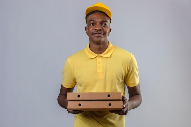 Dostawy Afroamerykanin W żółtej Koszulce Polo I Czapce Z Pudełkami Po Pizzy Z Pewną Siebie Stojącą Uśmiechem Darmowe Zdjęcia