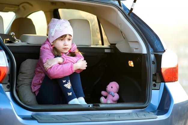 Dosyć Smutna Dziecko Dziewczyna Siedzi Samotnie W Bagażniku Samochodu Z Różowym Pluszowym Misiem. Premium Zdjęcia