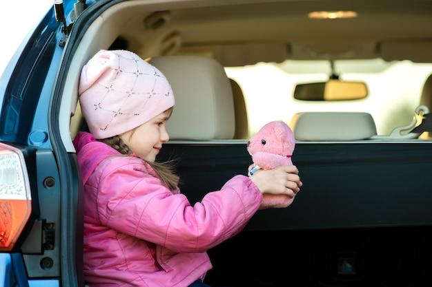 Dosyć Szczęśliwa Dziecko Dziewczyna Bawić Się Z Różowym Zabawkarskim Misiem W Bagażniku Samochodu. Premium Zdjęcia