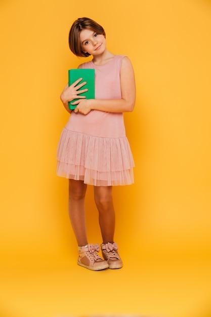 Dosyć Zadumanej Dziewczyny Przyglądająca Kamera I Mienie Zieleni Książka Odizolowywająca Darmowe Zdjęcia