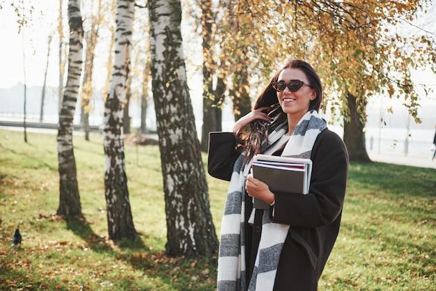 Dotyka Włosów Dłonią. Młoda Uśmiechnięta Brunetka W Okularach Przeciwsłonecznych Stoi W Parku Blisko Drzew I Trzyma Notepad Darmowe Zdjęcia
