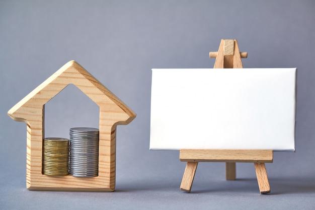 Drewniana figura domu z dwiema kolumnami wewnątrz i białą tablicą Premium Zdjęcia