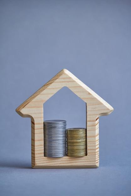Drewniana figurka domu i dwie kolumny monet wewnątrz na szarym tle. Premium Zdjęcia
