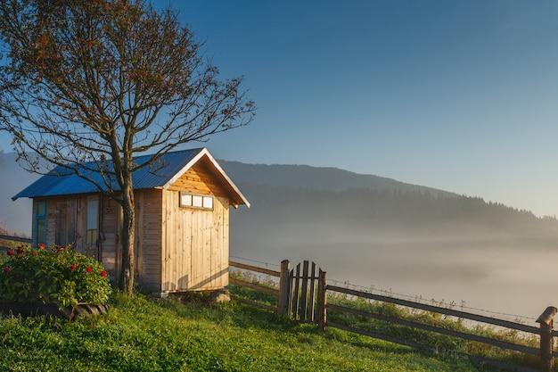 Drewniana kabina z ogrodzeniem i drzewem na odgórnym og wzgórzu w wschodzie słońca. góry Premium Zdjęcia