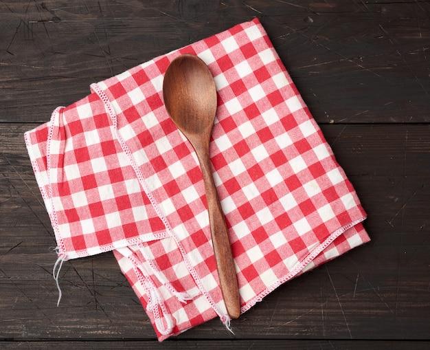 Drewniana łyżka I Czerwony Tekstylny Kuchenny Ręcznik Na Brown Drewnianym Tle Premium Zdjęcia