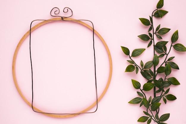 Drewniana rama w pobliżu sztucznej rośliny zielonej na różowym tle Darmowe Zdjęcia