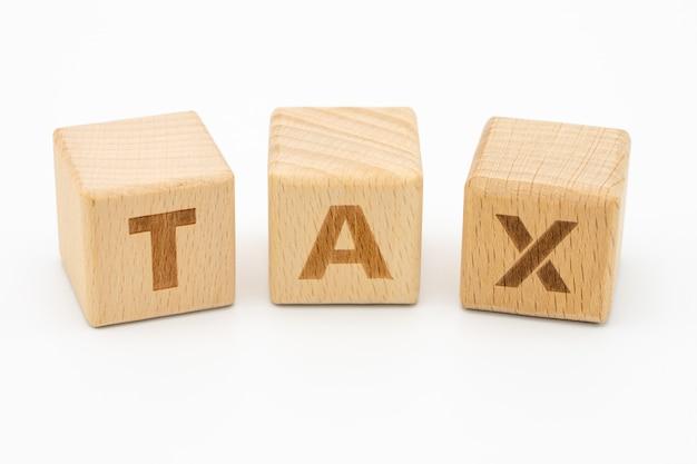 Drewniana słowo podatku pozycja na białym tle odizolowywa Premium Zdjęcia