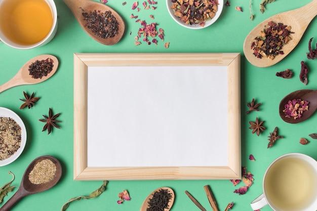 Drewniana Tablica Otoczona Różnymi Rodzajami Ziół Na Zielonym Tle Darmowe Zdjęcia