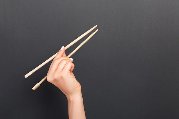 Drewniane Pałeczki W Kobiecej Dłoni I Czarne Tło Premium Zdjęcia