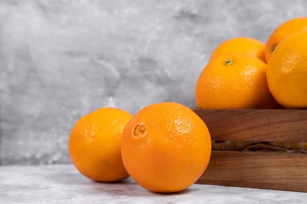 Drewniane Stare Pudełko Pełne Całych I Pokrojonych Pomarańczy Ułożonych Na Marmurze Darmowe Zdjęcia