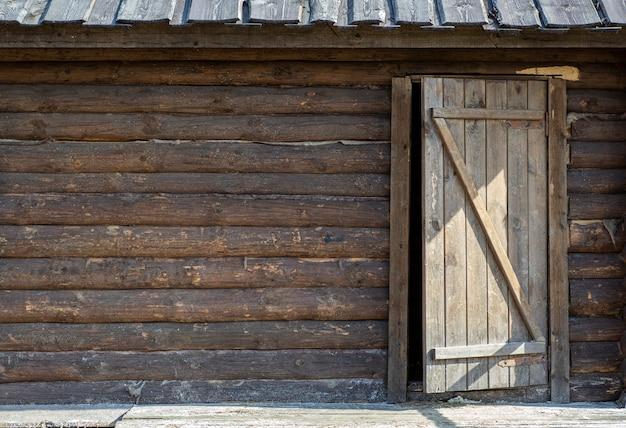 Drewniane Tła Z Drzwiami. Stara Drewniana ściana Nieociosany Dom Z Teksturą I Drzwi Premium Zdjęcia