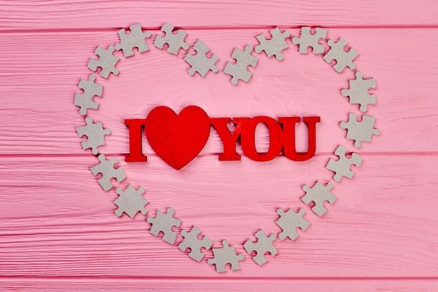 Drewniane Tło Walentynki. Czerwone Napisy Kocham Cię I Serce Wykonane Z Kartonowych Puzzli. Happy Valentines Wakacje. Premium Zdjęcia