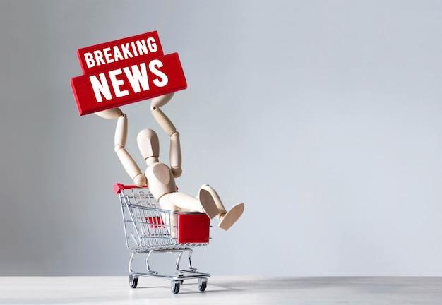 Drewniany Człowiek Posiada Czerwony Drewniany Klocek Ze Słowem Breaking News, Concept. Premium Zdjęcia