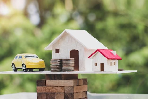 Drewniany dom, samochód z stos monet pieniędzy na drewnianym bloku Premium Zdjęcia