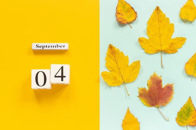 Drewniany Kalendarz 4 Września I żółte Jesienne Liście Na żółtym Niebieskim Tle. Premium Zdjęcia